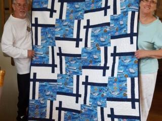 "Sue created this QOV for someone special. Crisp navy and white is always a winter. 20 – 13 ½"" blocks  54"" x 67.5""."